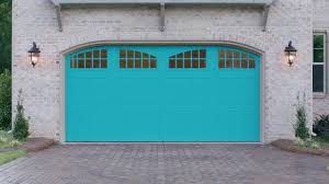 a white stone house has a robin s egg blue garage door with arch windows across the