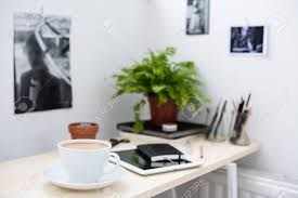 office working table. Cup Of Coffe In Bright And Modern Loft-style Office, Work Desk With Office Working Table E