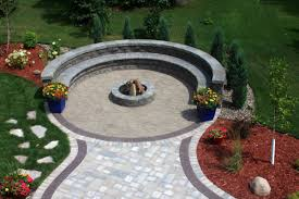 the circular patio created with unilock trevia pavers in oakwood adds contrasts and interest around the