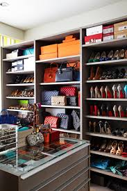 fantastic walk in closet design with gray cabinets filled with designer bags and shoes as well as gray closet island with glass top to easily view jewelry