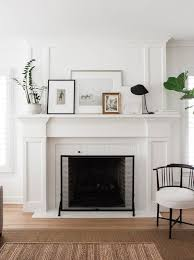 styling a mantle using layers of framed art work and a touch of greenery design by