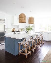 coastal kitchen with white cabinets blue island basket pendant lights bistro counter stools