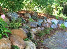 this retaining wall was built by omega in 2016 using seven tons of michigan fieldstone boulders hand picked from grand rapids gravel and planted using