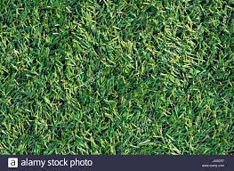 fake grass texture. Fake Grass Used On Sports Fields For Soccer, Baseball, Golf And Football. Closed-up Of Artificial Green Texture Background. Abstract Lawn.