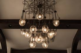 here the homeowner wanted a simple bistro feel so they chose a round capiz shell chandelier in gold it creates a lovely vignette with a touch of luxury