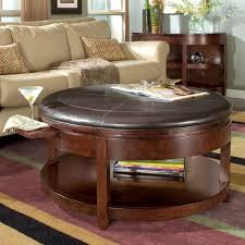 living room design with round coffee table ottoman and area rug also sectional sofa with credenza and window treatments