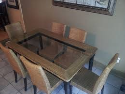 rectangle glass top table with brown rattan frame and black legs combined with brown rattan chairs light brown wooden