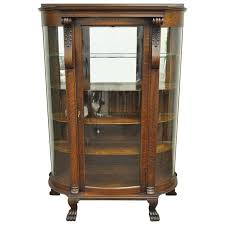 early 1900 approx date of manufacture intricate carving dark wood mahogany colour 4 shelves behind glass door bow fronted drawer section and lower
