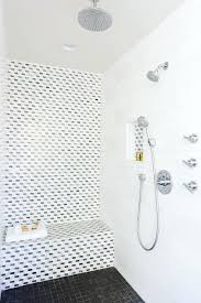 mosaic shower floor tile walk in shower boasts an accent wall clad in black and white mosaic marble tiles continuing on to a tiled shower bench