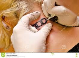 Tattoo Artist Drawing Tattoo Of Broken Chain On Girls Neck Stock