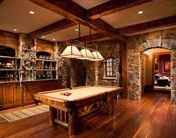 rec room lighting. beautiful stonework and floor in the game roombar area warm inviting lighting over pool table rec room
