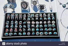 gemstone rings and other handcrafted silver items of navajo indian jewelry are displa to tourists along a roadside in arizona usa