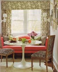 a saarinen inspired table adds mid century drama to this sunny dining nook the bold c fabric gives a jolt of energy to the clic camelback sofa and