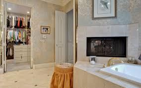 master bedroom bathroom fireplace black acrylic chair with metal leg furry animal skin rug patterned orange rug transpa glass shower door transpa