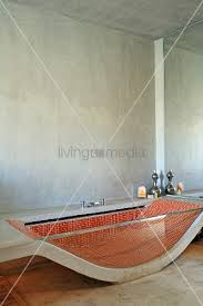 bathtub made from curved concrete slab and glass side wall with red mosaic tiles inside in minimalist bathroom 11273527