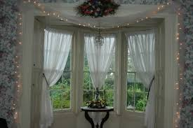 luxury bay window decoration white sheer curtains flower paterned wallpaper white framed windows lights surrounded