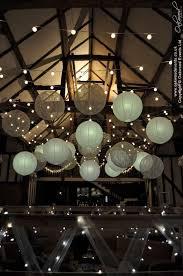 festoon lights and paper lanterns in the barn at hillfields farm perfect summer wedding lighting