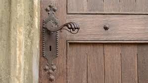 woman push the wrought iron door handle and opens an old wooden door after door is left open for entering can be used as a metaphor a new door is open