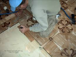 starting parquet installation tapping parquet tiles to insure adhesion tiles pushed together to minimize gaps