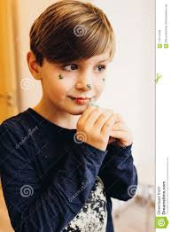 a cute boy paints his face with eatable color cream