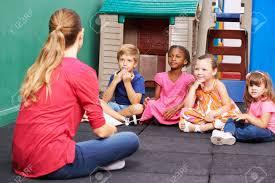 Nursery Teacher Discussion Group Of Children In Kindergarten Talking To Nursery