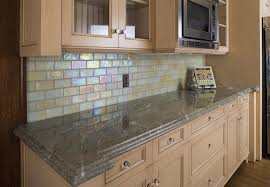 Glass tiles in types of shapes, like these in the form of subway tiles,  continues to be popular for kitchen backsplashes.