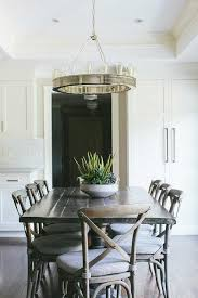fantastic dining room features a tray ceiling accented with a ralph lauren roark modular ring chandelier illuminating a dark plank dining table lined with