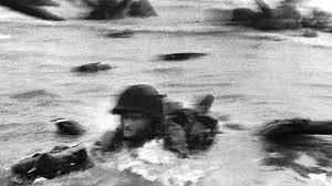 an american solr wades through water under heavy fire to reach the beach on the normandy coast of france on d day june 6 1944
