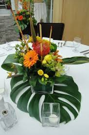 Add the banana leaf or monstera leaf underneath tropical floral centerpieces  makes them appear bigger.
