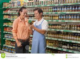 s clerk assisting women examining jar in the supermarket s clerk assisting women examining jar in the supermarket beijing stock photo 31693822 megapixl