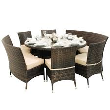 round glass top outdoor dining table feat three cushioned chairs plus two curved wicker benches with