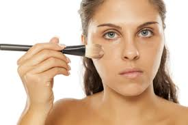 young beautiful woman applied liquid base with a brush