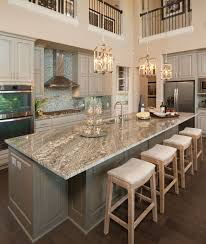 a large central kitchen island topped with brown granite