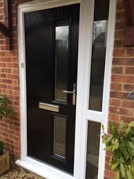black posite door with white frame and side panel to create a stylish modern entrance
