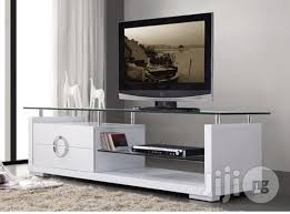 a brand new white tv stand with drawers and glass top