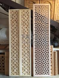 the two carved wood panels on the left will be used by a tazi designs client as double doors for a closet in a fairly contemporary home