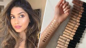 arshia moorjani with tousled hair and lowkey makeup and nyx concealer swatches on an arm and