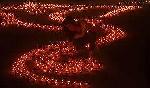 happy diwali a girl lights earthen lamps in a formation to form  happy diwali a girl lights earthen lamps in a formation to form the shape of