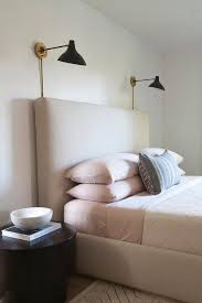 beige and pink bedroom features a beige bed dressed in pink bedding and a gray lumbar pillows lit by a pair of black and gold wall sconces flanked by round