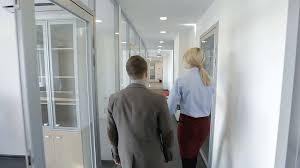 office corridor door glass. The Office Of Financial Company To New Male Employee. Businessman And Woman With Red Folder Are Going Throught Long Corridor Glass Door