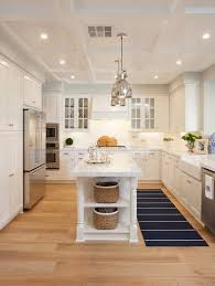 A pair of polished nickel industrial pendants hang over a narrow kitchen  island with turned legs