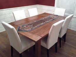 modern farmhouse dining table with burlap table runner and white leather dining chairs with high back and black wooden legs for small dining room spaces