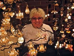 maria fowler of the little dolls house company toronto with a selection of miniature chandeliers
