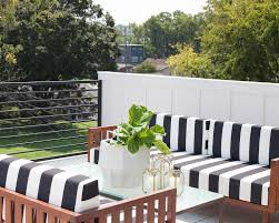a contemporary porch design combines black white and wood to create a homey vibe with two facing outdoor sofas