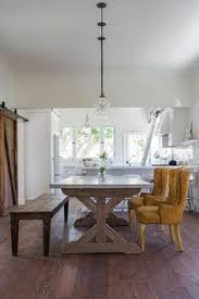 three clear gl barn light pendants illuminate a trestle dining table lined with mustard yellow tufted