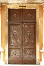 old double doors in dark brown tone with fading paint and no handle