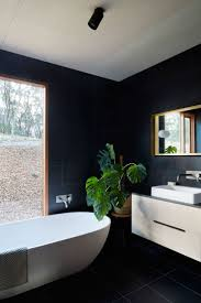 In this modern bathroom, large black tiles have been used on the walls and  floor