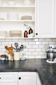 Subway tile w/ black grout, white cupboard, open shelving, darker countertop  Before