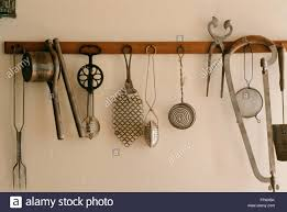 vintage kitchen tools. stock photo - vintage kitchen gadgets hanging from a rack tools