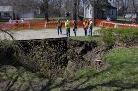 des moines city officials evaluate a sinkhole that formed on a lawn in a south side residential neighborhood